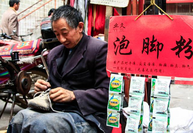 Hombre tibetano realizando su trabajo en la vereda de la calle principal de Danba