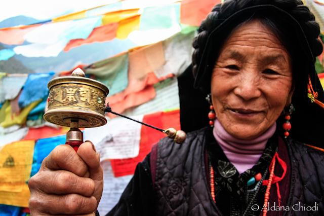 Mujer tibetana con rueda de oración